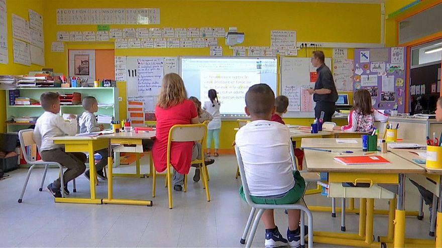 Des élèves d'une école primaire écoute leur instituteur en classe