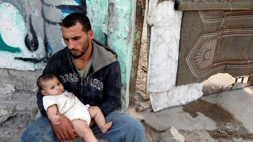 فلسطيني يحمل طفلا داخل مخيم للاجئين في غزة يوم السبت.