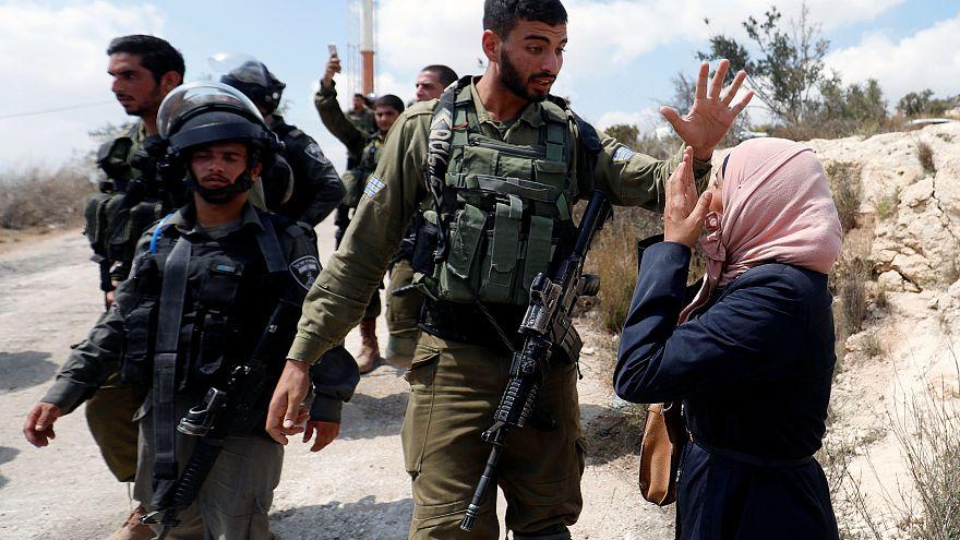 Una mujer palestina frente a un soldao israelí en la aldea de Ras Karkar