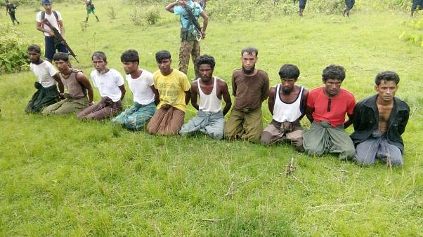 Rohingya men kneel with hands bound as a paramilitary officer stands guard.