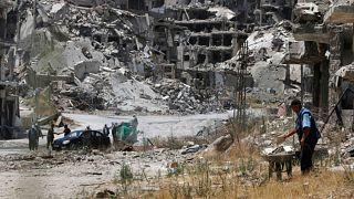 عمال يجمعون حطام مبان دمرت لاستخدامها من جديد