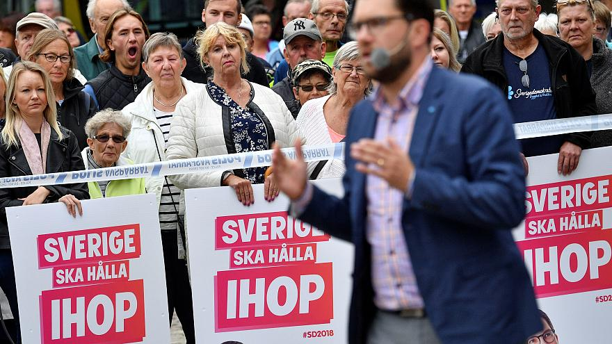 Voters look on as Sweden Democrats leader Jimmie Akesson gives a speech