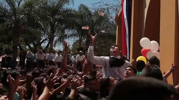 Cientos de niños a la caza de billetes en una fiesta religiosa en Paraguay