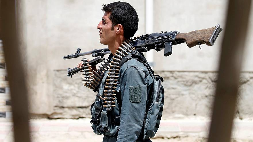 An Afghan policeman keeps watch during a battle with insurgents in Kabul.