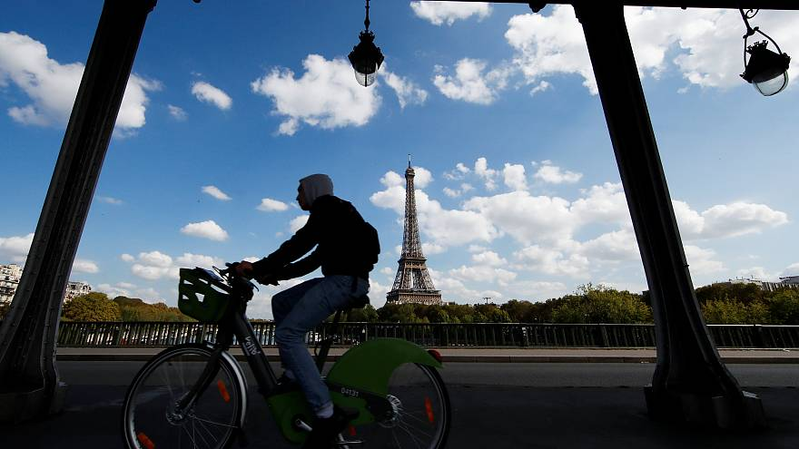 Un hombre cruza un puente en bicicleta cerca de la Torre Eiffel en París