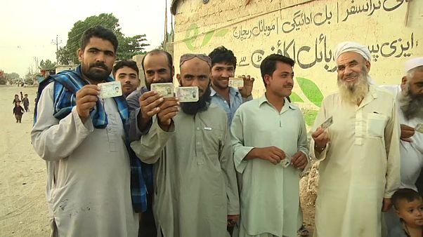 مواطنون أفغان يحملون بطاقات هوية كلاجئين في أحد معسكرات اللاجئين في باكستان