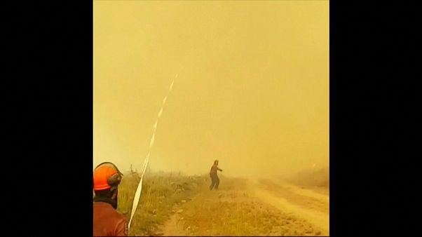 Un tornado de fuego absorbe la manguera de un equipo de bomberos