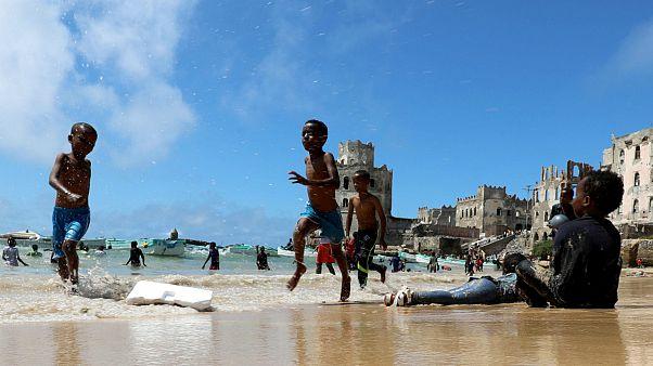 Crianças brincam em Mogadíscio, Somlia, na rebentação do oceano Índico