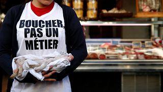 Une manifestante antispéciste devant une boucherie