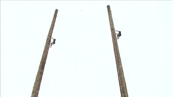 Zwei Männer klettern an Pfählen hoch