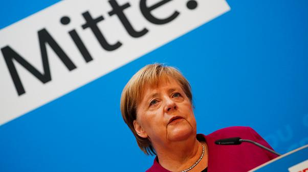 """Angela Merkel bei einer Rede; im Hintergrund das Wort """"Mitte"""""""