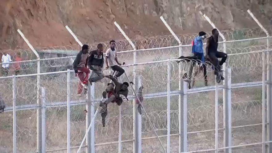 Inmigrantes africanos en la valla fronteriza en Ceuta.