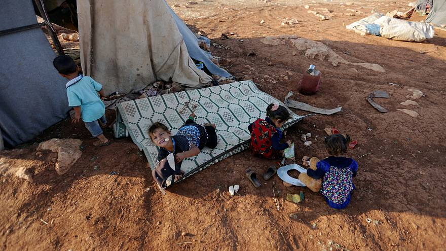 Newly displaced Syrian children play after their arrival to a camp in Idlib