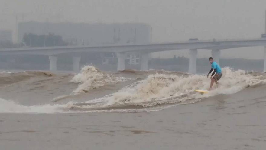 Surfers from around the world gather to ride tidal bores of the Qiantang River