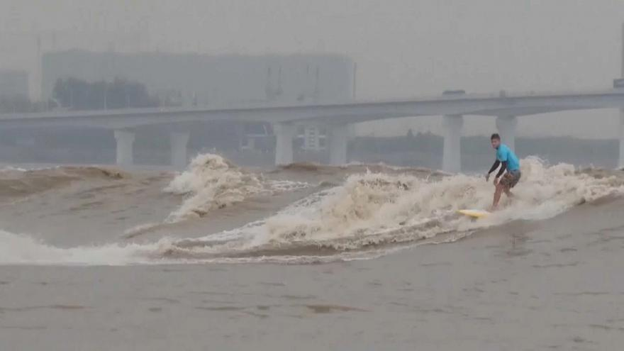 Des surfeurs tentent de dompter la vague géante du fleuve Qiantang en Chine