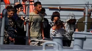 Migrants arrive on a patrol boat after being transferred from Aquarius