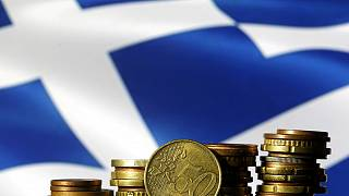 FILE PHOTO: Euro coins are seen in front of a displayed Greece flag in this picture illustration, June 29, 2015. REUTERS/Dado Ruvic/File Photo