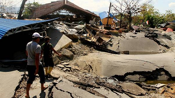 People walk in an area hit by an earthquake in Palu, Indonesia