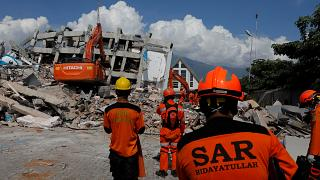 Rescuers on Sulawesi Island, Indonesia work in the rubble of a hotel