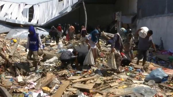 Aid slowly delivered to Indonesia quake and tsumani victims, some forage for food