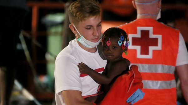 Un miembro de la Cruz Roja lleva a un niño migrante en brazos.