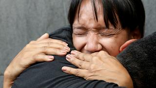 Mourners react outside National Intelligence Service building in Caracas