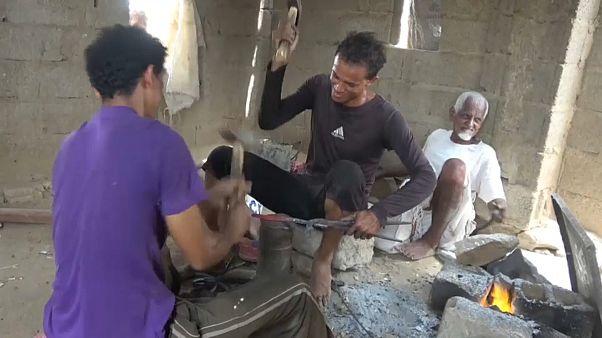 صورة حرفيين يصنعان خنجراً من شظايا القذائف والصواريخ في محافظة حجة باليمن