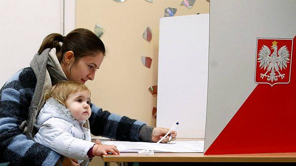 Mãe e filho numa mesa de voto das autárquicas polacas