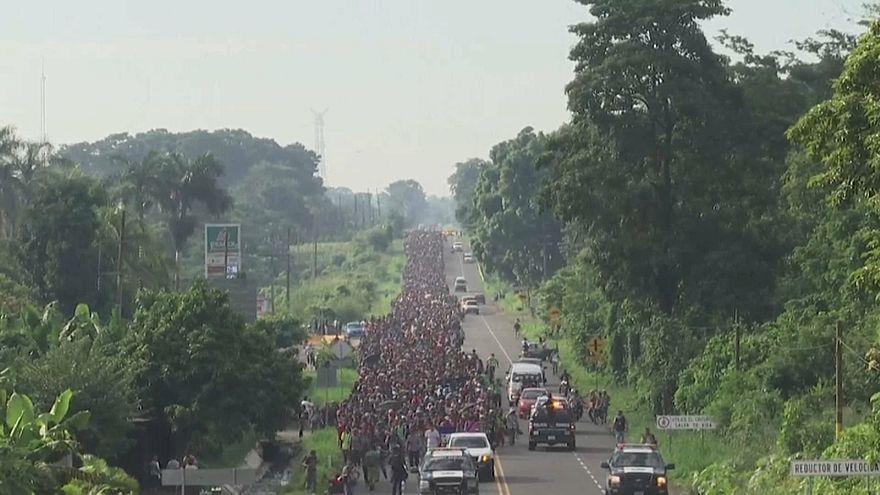Tausende zentralamerikanische Migranten laufen auf einer Straße.