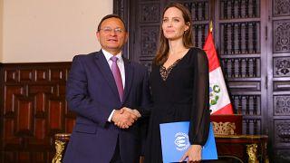 Angelina Jolie und Perus Außenminister Nestor Popolizio schütteln Hände