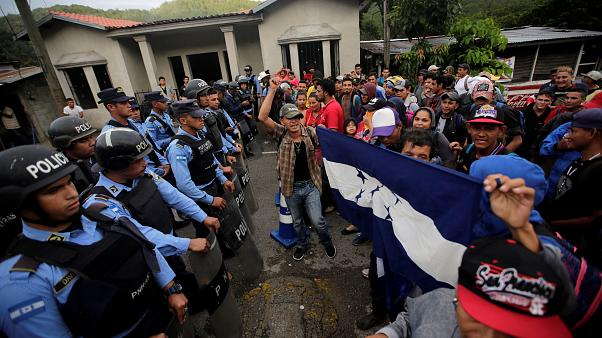 Migrants are confronted by police at the Honduras-Guatemala border