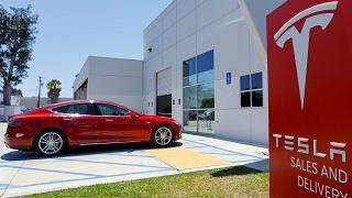 Ein roter Tesla und ein Schild mit dem Tesla-Logo