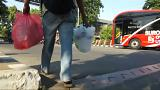 Screencapture showing an Indonesia man bringing plastic bottles to a bus