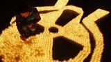 Un militant anti-nucléaire éclaire un symbole