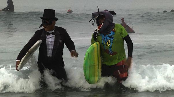 Surfistas disfrazados festejan Halloween sobre las olas en Newport Beach