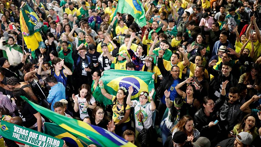 Supporters of Jair Bolsonaro react after Bolsonaro wins the presidential ra