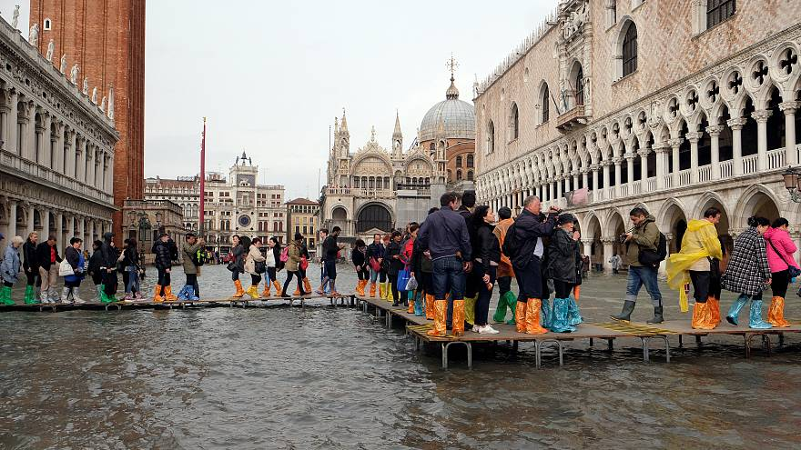 Tourists walk in a flooded Saint Mark Square