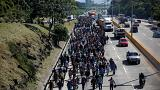 People walk in a caravan of migrants en route to the US in El Salvador.