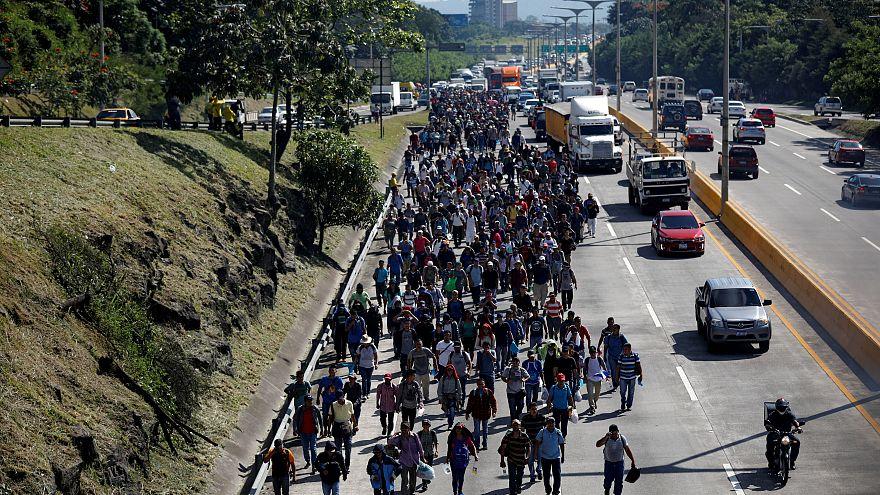 People walk in a caravan of migrants en route to the US in El Salvador.