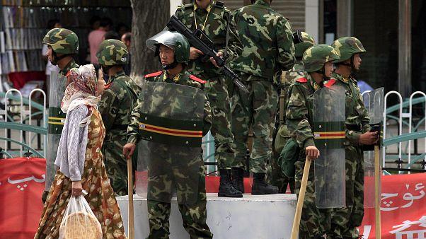 Doğu Türkistan'ın Urumçi kentinde, Çinli askerlerin önünden geçen Uygur kadın