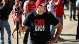 "A man wearing a ""fake news"" T-shirt"