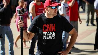 """A man wearing a """"fake news"""" T-shirt"""