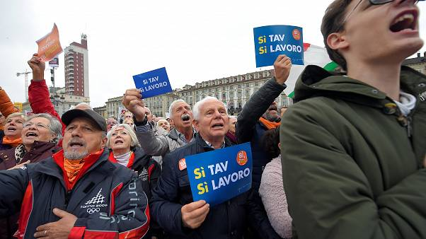 """A man holds a placard reading """"Yes Tav, Yes job"""""""