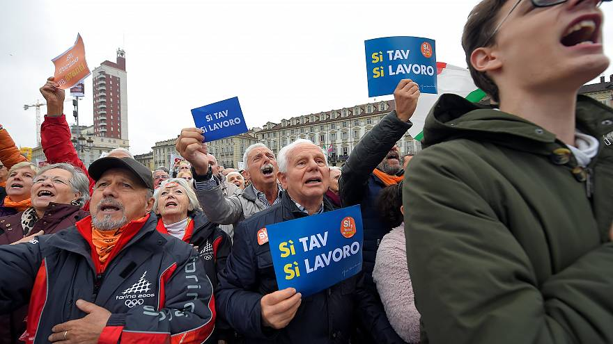 "A man holds a placard reading ""Yes Tav, Yes job"""