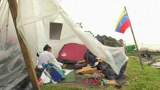 Venezolanische Migranten in einem Zelt, daneben die ven. Flagge