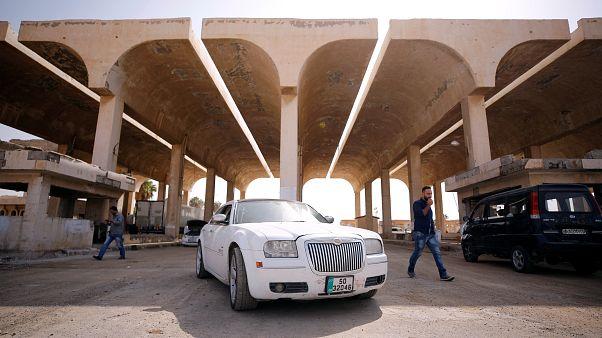 Ein jordanisches weißes Auto steht vorm Grenzübergang