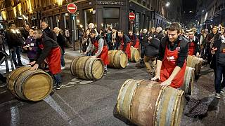 Men roll barrels of Beaujolais Nouveau wine