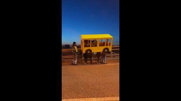 شاهد: شباب يتنكرون بزي حافلة ليتمكنوا من عبور جسر محظور على المشاة في روسيا