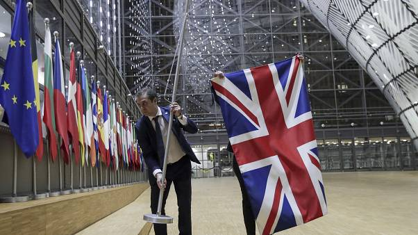 Members of protocol remove the Union flag from the atrium of the Europa building in Brussels, Friday, Jan. 31, 2020.