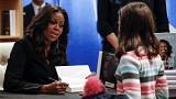 "Former first lady Michelle Obama signs a copy of her memoir ""Becoming""."